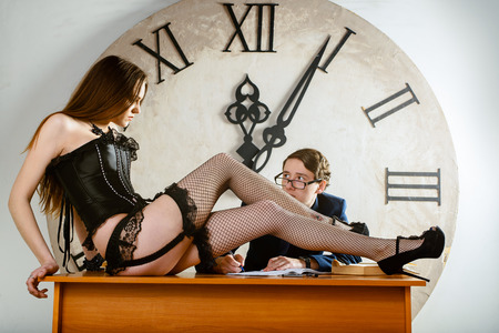 Sexy Woman Is a Present For a Student. Sexy Woman On a Table In Front of Man Studying And Take notes Late At Night. Girl Friday is on the table in front of man. Two Shot