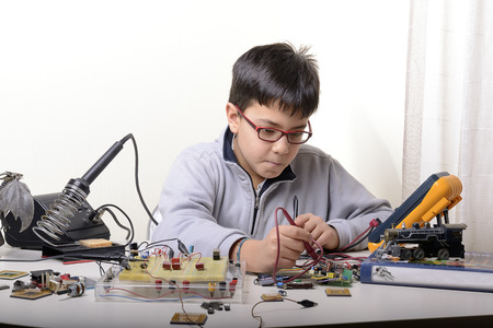 Photo pour Young student performs experiments in electronics and dreams of the future. - image libre de droit