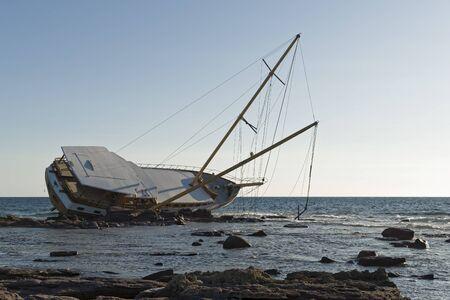 Photo pour Sailboat, stranded along the coast on the cliff of Sardinia in the Mediterranean Sea. - image libre de droit