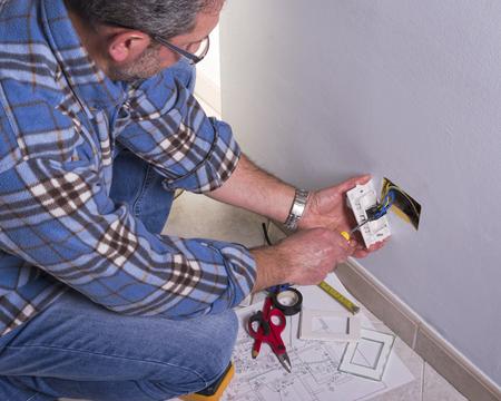 Foto de Electrician's hands assembles a standard bipolar wall socket. - Imagen libre de derechos