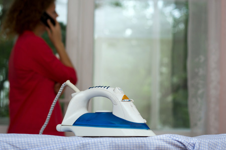 Photo pour Girl talking on the phone forgetting about the iron on the ironing board - image libre de droit