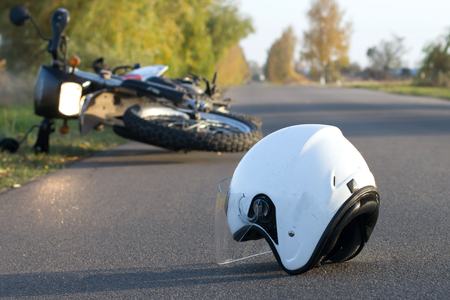 Photo pour Photo of helmet and motorcycle on road, the concept of road accidents - image libre de droit