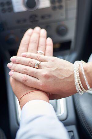 Foto de Newlyweds in the car show hands with wedding rings on the fingers, close-up. - Imagen libre de derechos
