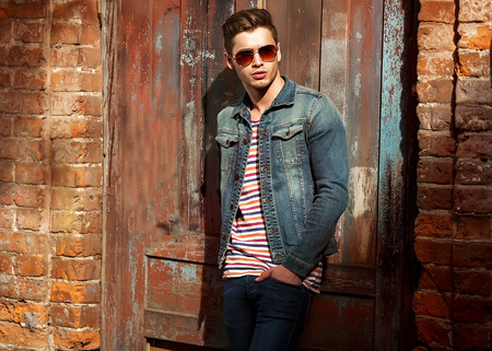 Foto de Hipster style guy. Fashion man standing near a wooden door - Imagen libre de derechos