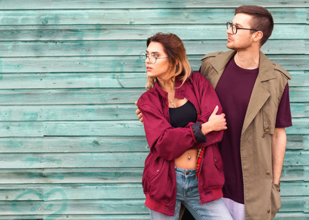 Photo pour fashion couple in their glasses with burgundy clothes posing on a blue wooden wall - image libre de droit