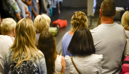 Foto de People wait with Luggage at airport, view from the back. Blurry. - Imagen libre de derechos