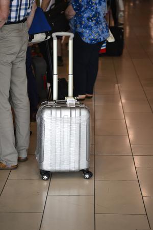 Foto de A man with a big silver suitcase on wheels in anticipation of boarding the plane. Blurry. - Imagen libre de derechos
