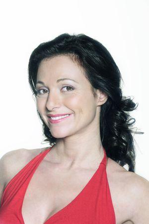 Foto de portrait on white background of a forty years old woman in studio smiling wearing a red dress  - Imagen libre de derechos