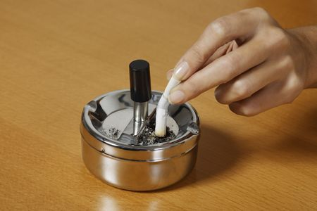 Photo for hand crushing a cigarette on an ash tray on a table - Royalty Free Image