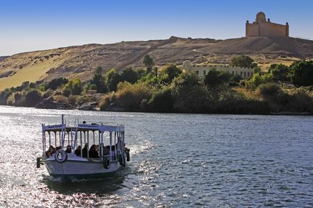 Photo pour  boat cruising on the river nile with Aga Khan tomb on the shore near aswan in egypt - image libre de droit
