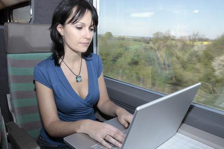 Photo pour beautiful young woman woman in a train using a computer lap top - image libre de droit