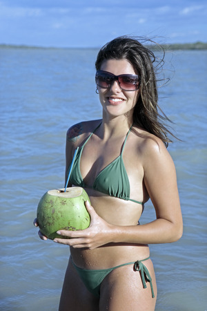 Photo pour beautiful smiling bikini dressed young brazilian  woman drinking and holding fresh coconut juice in the tatajuba lagoon in jericoacoara ceara state near fortaleza - image libre de droit