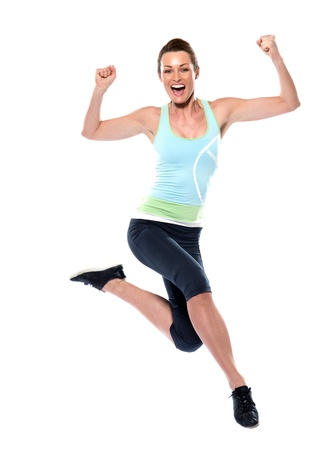 woman running sportswear happy jumping on studio white isolated background