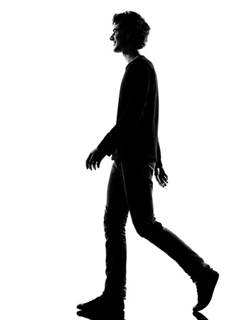 Photo for young man smiling walking silhouette in studio isolated on white background - Royalty Free Image