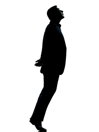 Photo for one caucasian business man silhouette standing tiptoe looking up Full length in studio isolated on white background - Royalty Free Image