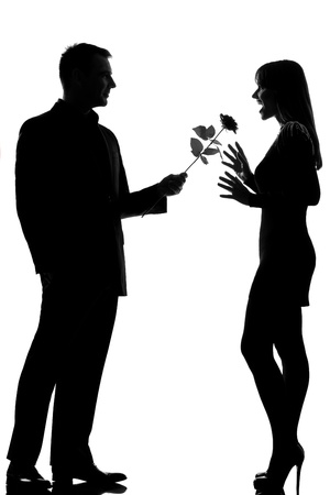 Photo for one caucasian lovers couple man offering rose flower and woman surprised in studio silhouette isolated on white background - Royalty Free Image