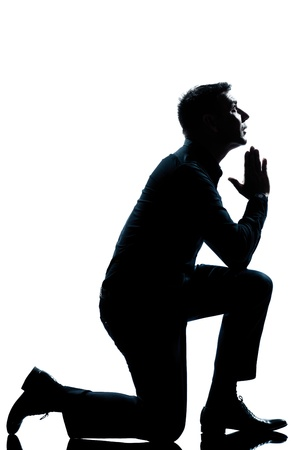 Photo for one caucasian man kneeling praying  full length silhouette in studio isolated white background - Royalty Free Image