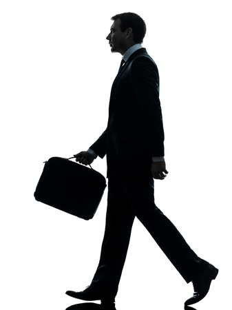 Photo for one caucasian businessman walking side view in silhouette studio isolated on white background - Royalty Free Image