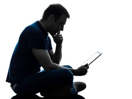 Foto de one caucasian man  sitting holding digital tablet   in silhouette on white background - Imagen libre de derechos