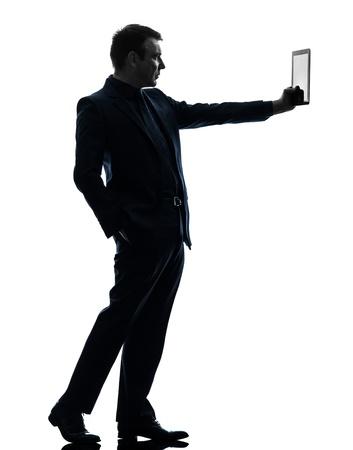 Foto de one caucasian business man holding digital tablet   in silhouette on white background - Imagen libre de derechos