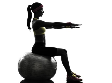 one  woman exercising fitness workout on fitness ball in silhouette  on white background mural