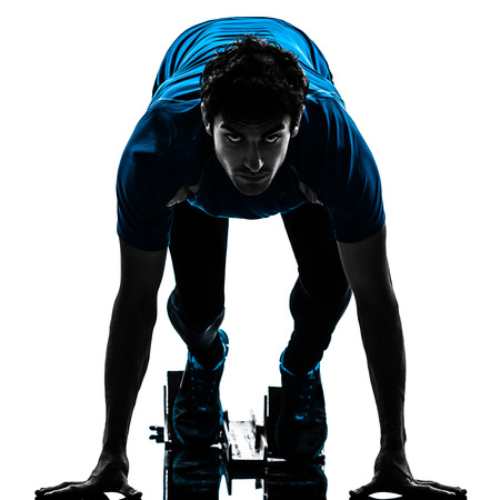 Foto de one caucasian man runner sprinter on starting blocks  in silhouette studio isolated on white background - Imagen libre de derechos