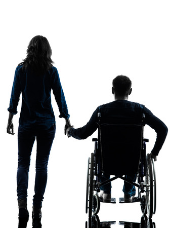 Foto de one handicapped man and woman holding hands in silhouette studio  on white background - Imagen libre de derechos