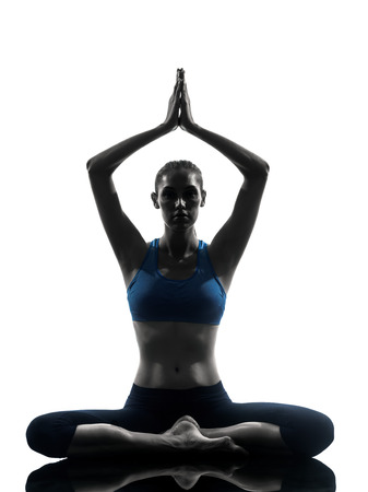 Foto de one caucasian woman exercising yoga meditating sitting hands joined in silhouette studio isolated on white background - Imagen libre de derechos