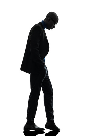 Photo for one african  black man standing looking down  in silhouette studio on white background - Royalty Free Image