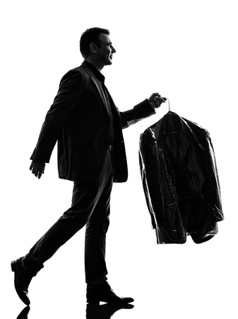 Foto de one caucasian business man holding dry clean clothes in silhouette  on white background - Imagen libre de derechos