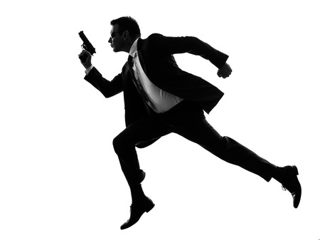 Photo pour one caucasian man running with handgun  in silhouette  on white background - image libre de droit