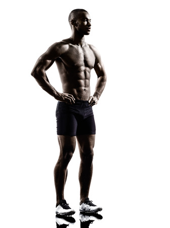 Photo for one young african muscular build man standing topless silhouette  isolated on white background - Royalty Free Image