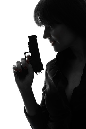 Photo for one caucasian sexy detective woman holding aiming gun in silhouette studio isolated on white background - Royalty Free Image