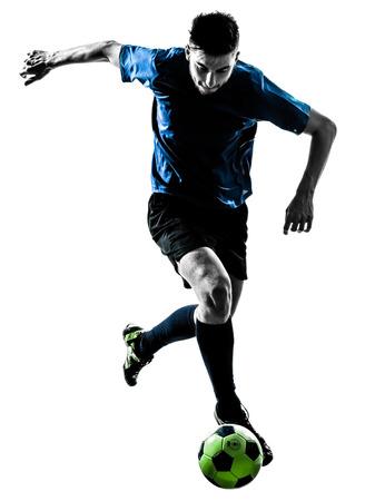Foto de one caucasian soccer player man juggling ball in silhouette isolated white background - Imagen libre de derechos