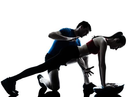 Foto de personal trainer man coach and woman exercising abdominals push ups on bosu silhouette studio isolated on white background - Imagen libre de derechos