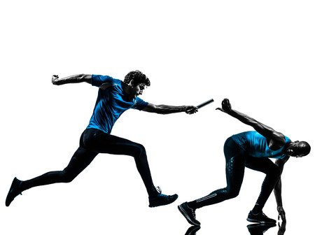 Foto de two men relay running sprinting in silhouette studio isolated on white  - Imagen libre de derechos