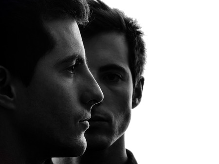 Foto de close up portrait two  young men in shadow white background - Imagen libre de derechos