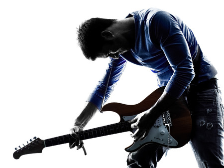 Photo pour one caucasian man electric guitarist player playing in studio silhouette isolated on white background - image libre de droit