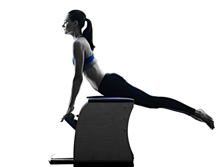 Photo pour one caucasian woman exercising pilates chair exercises fitness in silhouette isolated on white backgound - image libre de droit