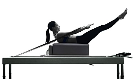Photo for one caucasian woman exercising pilates reformer exercises fitness in silhouette isolated on white backgound - Royalty Free Image