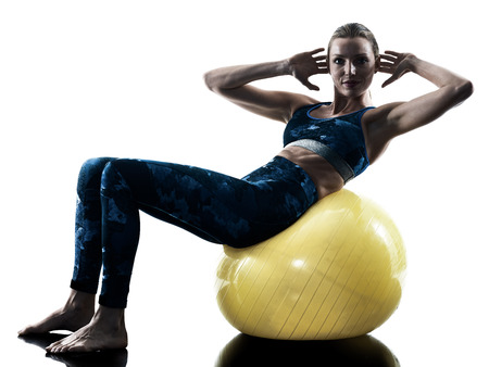 Photo for one caucasian woman exercising fitness swiss ball excercises in silhouette isolated on white background - Royalty Free Image