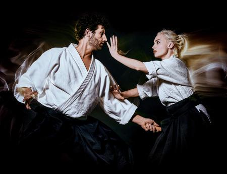 Foto de two bodokas fighters man and woman practicing Aikido studio shot isolated on black background - Imagen libre de derechos