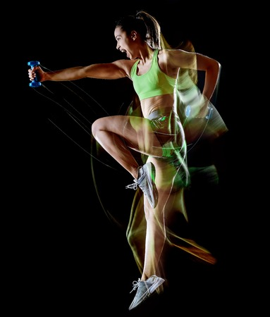 Foto de one mixed race woman exercising fitness exercises isolated on black background with lightpainting effect - Imagen libre de derechos