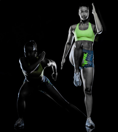 Foto de one mixed race woman exercising fitness exercises isolated on black background with lightpainting effect multiple exposures - Imagen libre de derechos