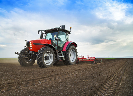 Photo for Farmer in tractor preparing land for sowing - Royalty Free Image