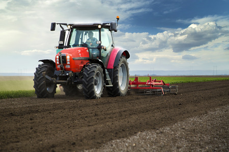 Photo for Close-up of griculture red tractor cultivating field over blue sky - Royalty Free Image