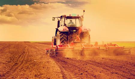 Foto de Farmer in tractor preparing land for sowing - Imagen libre de derechos