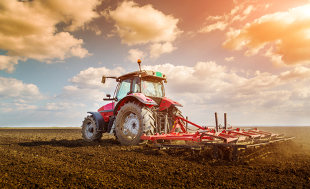 Photo for Farmer in tractor preparing land with seedbed cultivator - Royalty Free Image