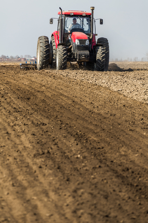 Photo pour Tractor cultivating field at spring - image libre de droit