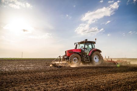 Photo pour Tractor cultivating field at spring - image libre de droit